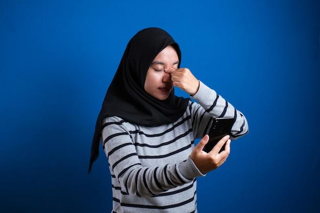 Azjatycka muzułmańska nastolatka trzymająca się za głowę i zamykająca oczy, bolesny wyraz z powodu bólu głowy lub stresu emocjonalnego