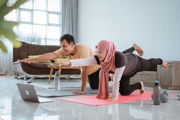 Azjatycka muzułmańska para fitness rozciągająca się i patrząc na samouczek wideo online przez laptopa