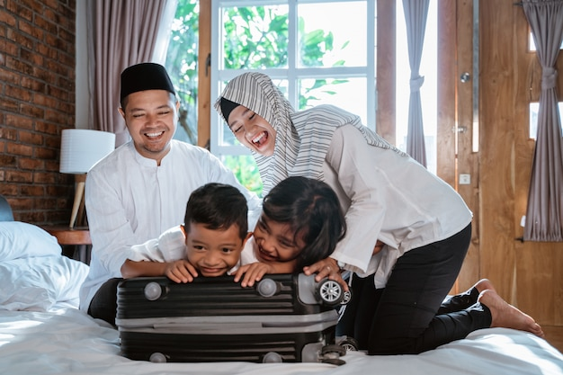 Azjatycka muzułmańska rodzina przygotowuje walizkę do noszenia, gdy mudik
