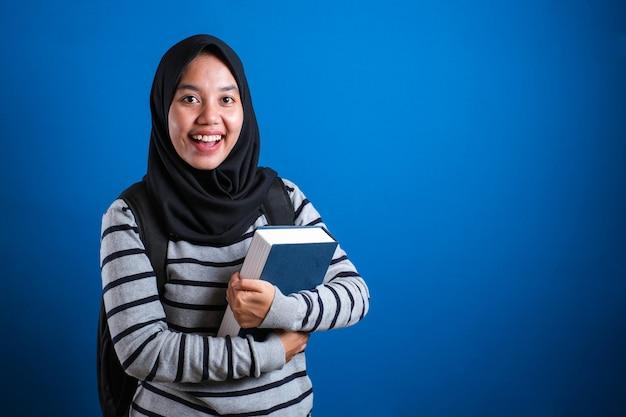 Azjatycka muzułmańska studentka ubrana w hidżab uśmiechnięta przyjazna trzymająca dużą książkę
