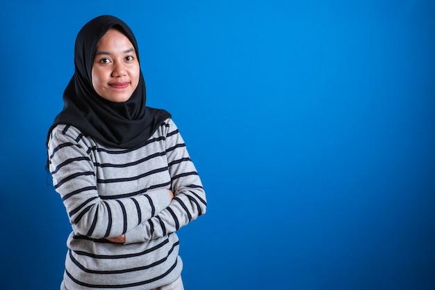 Azjatycka muzułmańska studentka ubrana w hidżab, uśmiechnięta przyjaźnie z rękami skrzyżowanymi na niebieskim tle