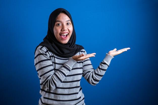 Azjatycka muzułmańska studentka uśmiechnięta i wskazująca na prezentowanie czegoś na boku z miejscem na kopię