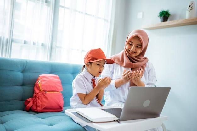 Azjatycka muzułmańska uczennica modli się przed rozpoczęciem zajęć online z domu