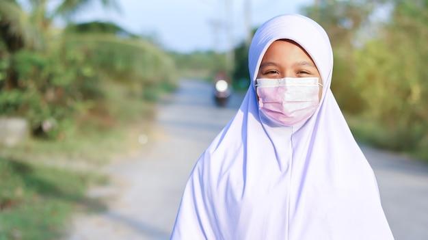 Azjatycka muzułmańska uczennica nosząca hidżab i maskę na twarz, aby zapobiec covid-19