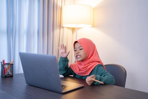 Azjatycka muzułmańska uczennica szkoły podstawowej wita się ze swoim przyjacielem i nauczycielem podczas internetowej konferencji klasowej