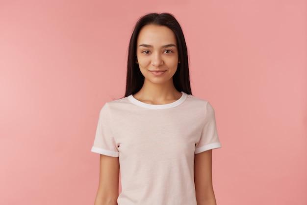 Azjatycka nastolatka, pewnie patrząc kobieta o ciemnych długich włosach. ubrana w białą koszulkę. koncepcja ludzi i emocji. oglądanie i uśmiechanie się na białym tle nad pastelową różową ścianą
