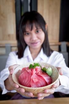 Azjatycka nastolatka pokazuje, że maguro lub tuńczyk don to surowe maguro lub tuńczyk z ryżem z przodu, patrząc w kamerę i uśmiechając się w japońskiej restauracji. selektywna ostrość.