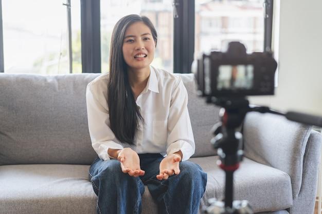 Azjatycka nastolatka rozmawia z kamerą i nagrywa materiał do klipu w mediach społecznościowych