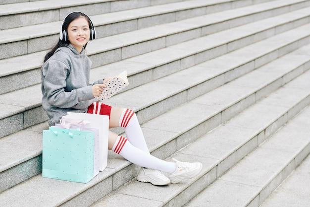 Azjatycka nastolatka siedząca na schodach obok toreb z zakupami i czytająca ciekawą książkę