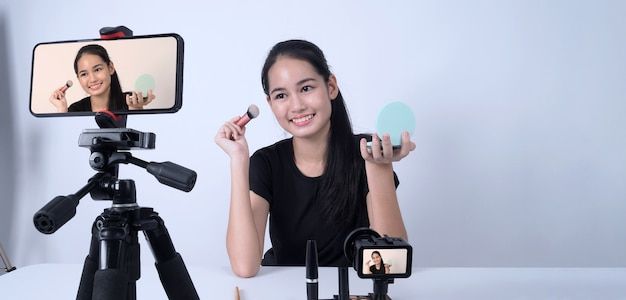 Azjatycka nastolatka siedzi przed kamerą i transmituje na żywo jako wpływowa blogerka kosmetyczna lub youtube, aby przejrzeć lub doradzić, jak makijaż w domu.