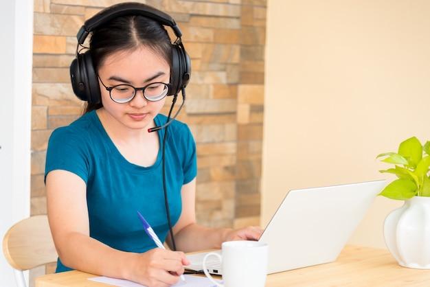 Azjatycka nastolatka studentka z zestawem słuchawkowym przyjmuje notatkę nauczoną online ze szkoły w zeszycie za pomocą laptopa. kształcenie na odległość z klasy uczelni poprzez wideorozmowę z domu