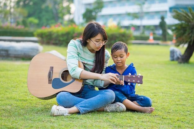 Azjatycka nastoletnia dziewczyna uczy gitarę dla chłopiec z czule i zabawą w zielonych łąkach