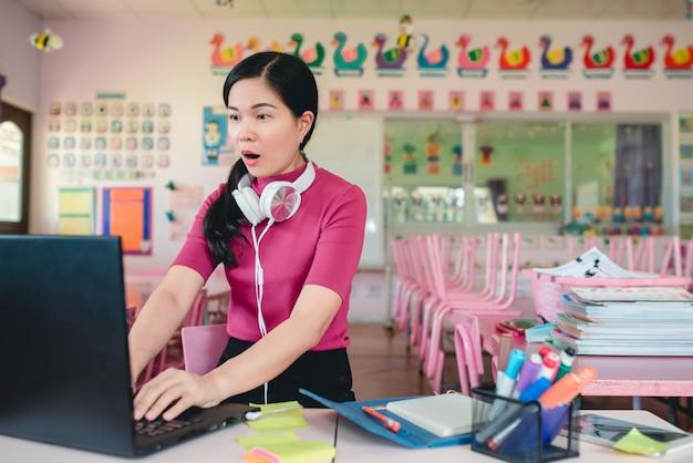 Azjatycka nauczycielka przedszkolna uczy uczniów w przedszkolu online. nauczyciele i uczniowie używają internetowych systemów wideokonferencyjnych do nauczania uczniów.