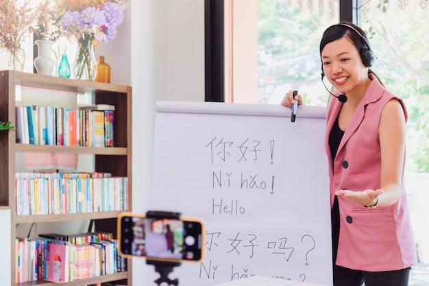 Azjatycka nauczycielka uczy zdalnie w domowym biurze za pomocą smartfona technologii online.