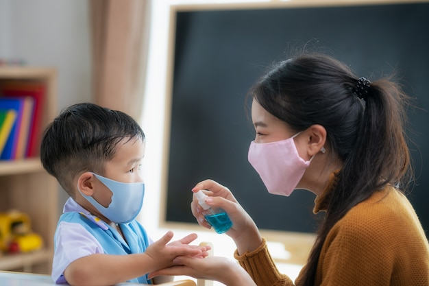 Azjatycka nauczycielka używa sprayu do rąk swojego ucznia