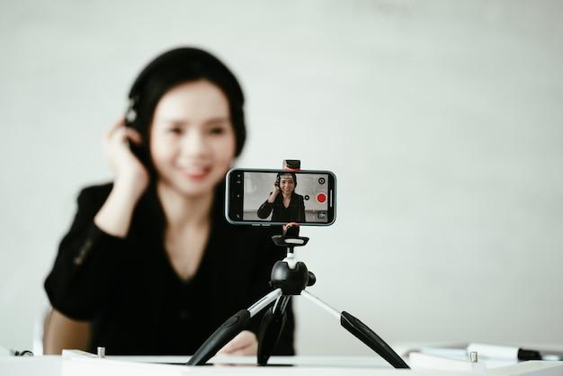 Azjatycka nauczycielka w średnim wieku mieszka na uniwersytecie online ze smartfonem