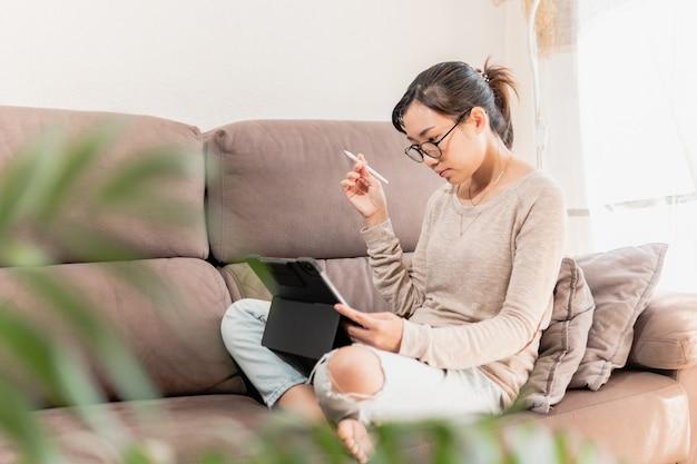 Azjatycka niezależna projektantka graficzna dziewczyna myśli i szuka inspiracji siedząc na sofie z tabletem.