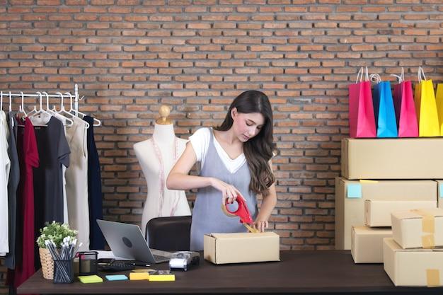 Azjatycka niezależna sprzedawca przygotowuje produkt do pakowania w domu. sprzedaż online
