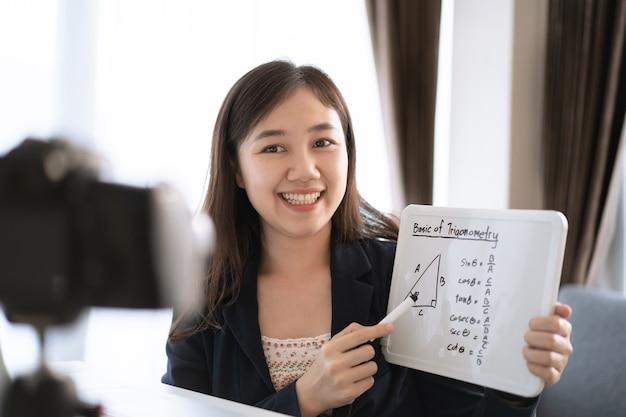 Azjatycka osoba z bloga wideo lub vlog jest teraz na żywo w internecie za pośrednictwem laptopa i kamery wideo, osoby mające wpływ na sieć społecznościową, która transmituje na żywo w internecie. wykładowca matematyki online.