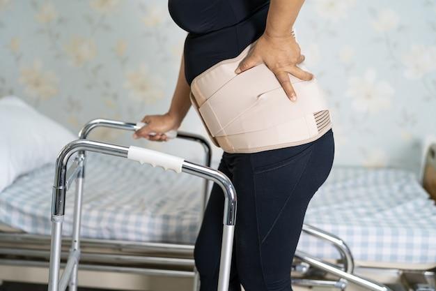 Azjatycka pani pacjentka nosząca pas podtrzymujący ból pleców dla ortopedycznego odcinka lędźwiowego z chodzikiem.