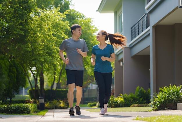 Azjatycka para biega w sąsiedztwie, aby zapewnić sobie codzienne zdrowie i dobre samopoczucie, zarówno fizyczne, jak i psychiczne oraz proste antidotum na codzienne stresy i bezpieczne kontakty towarzyskie.