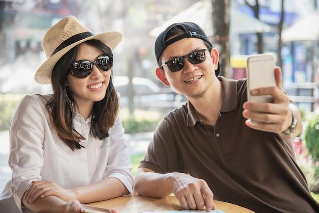 Azjatycka para cieszy się podróżować obsiadanie przy sklep z kawą