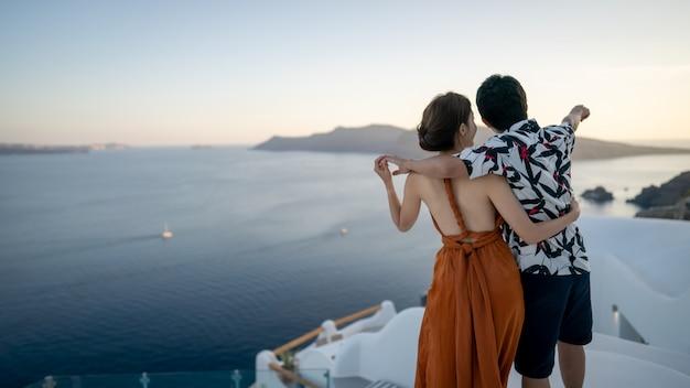 Azjatycka para cieszy się widoku oia wioskę w santorini wyspie, grecja.