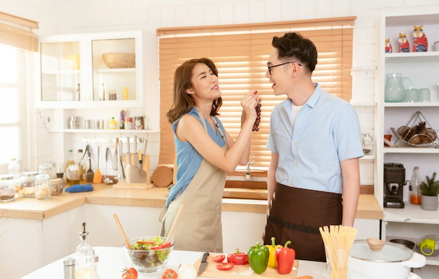Azjatycka para cieszy się wspólne gotowanie sałatki w kuchni w domu.