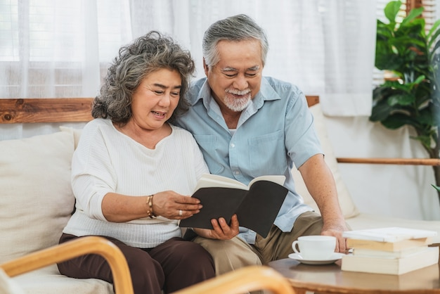 Azjatycka para dziadkowie siedzący i czytający książkę razem z radosnym uczuciem w domu