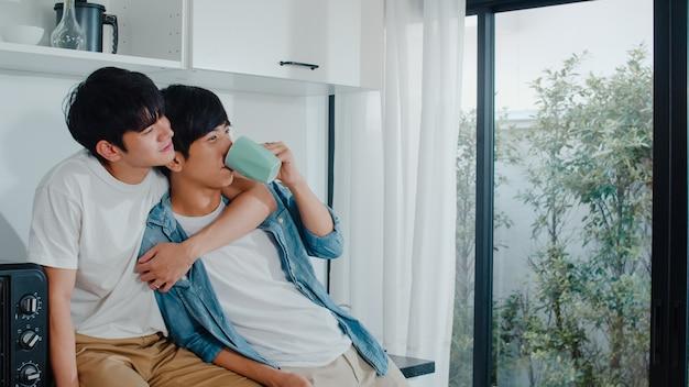 Azjatycka para homoseksualistów pije kawę i świetnie się bawi w domu. młodzi przystojni mężczyźni lgbtq + rozmawiają szczęśliwie odpoczywają razem spędzają romantyczny czas w nowoczesnej kuchni w domu rano.