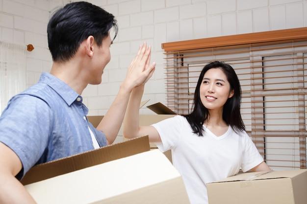 Azjatycka para kupuje nowy dom, trzyma papierowe pudełko, żeby włożyć rzeczy. przeprowadzka się do nowego domu. koncepcja rozpoczęcia nowego życia, stworzenia rodziny.
