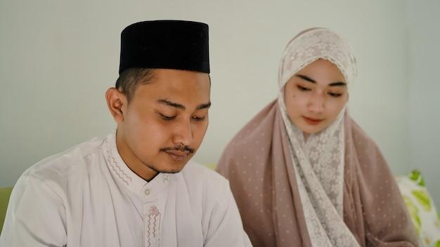 Azjatycka para muzułmańska modli się razem w domu