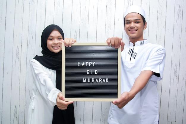 Azjatycka para muzułmańska trzymająca tablicę z literami mówi happy eid mubarak