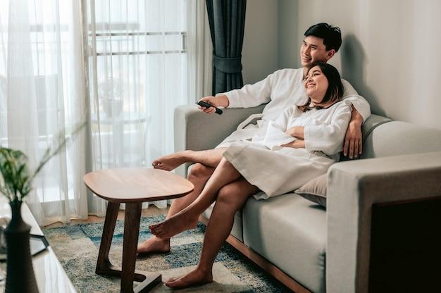 Azjatycka para oglądająca telewizję siedząca na kanapie w salonie w domu