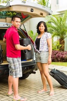 Azjatycka para pakuje samochód z walizkami na wakacje