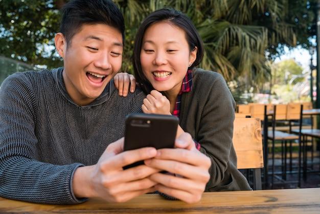 Azjatycka para patrzeje telefon komórkowego.