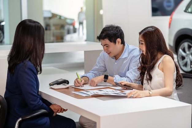 Azjatycka para podpisuje umowę ze sprzedawczynią po podjęciu decyzji o zakupie nowego samochodu w salonie