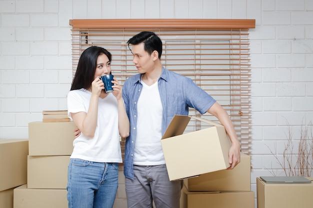 Azjatycka para przeprowadza się do nowego domu w pokoju było wiele dużych brązowych kartonowych pudeł. koncepcja rodziny szczęśliwa para czuje się usatysfakcjonowana przeniesiona do nowego domu, aby zbudować rodzinę.