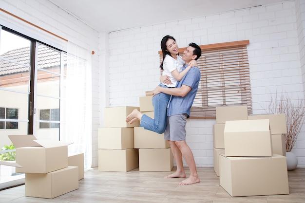 Azjatycka para przeprowadzająca się do nowego domu skacząc razem radośnie na podłodze pokoju leżało duże brązowe kartonowe pudło. koncepcja rodziny para przeniosła się do nowego domu, aby zbudować rodzinę.