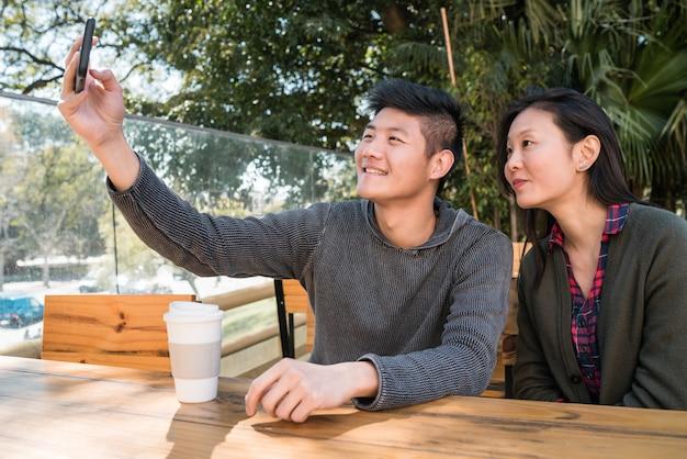 Azjatycka para przy selfie z telefonem komórkowym.