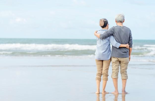 Azjatycka para seniora spaceru na plaży, trzymając się za ręce. miesiąc miodowy rodzina razem szczęścia styl życia. życie po przejściu na emeryturę. ubezpieczenie na życie
