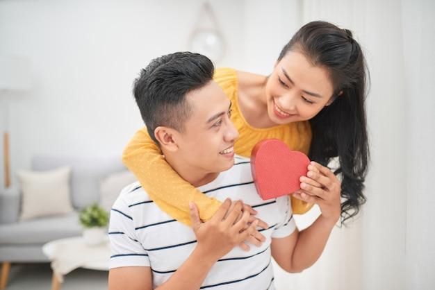 Azjatycka para siedząca na kanapie daje czerwone pudełko na prezent w wyjątkowy dzień