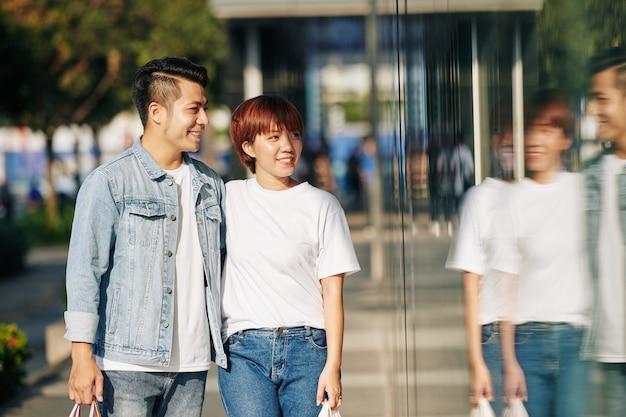 Azjatycka para spacerująca wzdłuż ulicy