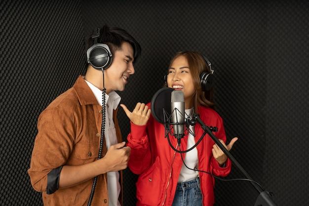 Azjatycka para śpiewaków w studiu nagraniowym używająca mikrofonu studyjnego z pasją w studiu nagrań muzycznych