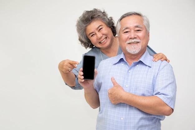 Azjatycka para starszy kobieta pokazuje lub prezentuje aplikację telefonu komórkowego pod ręką na białej ścianie