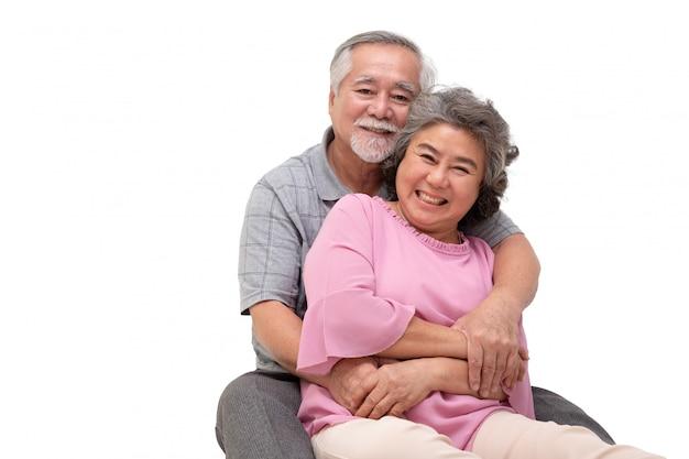 Azjatycka para starszy siedzi i przytulanie razem na białym tle.