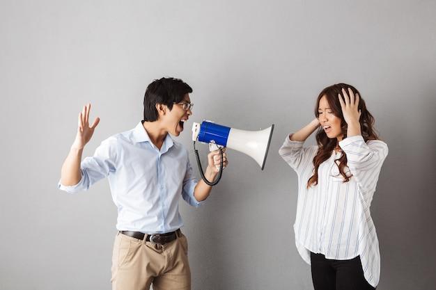 Azjatycka para stoi, mężczyzna krzyczy do głośnika