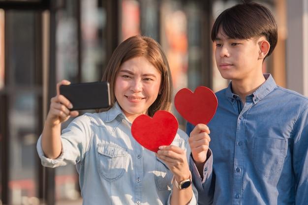 Azjatycka para trzyma czerwone serce szczęśliwy w miłości