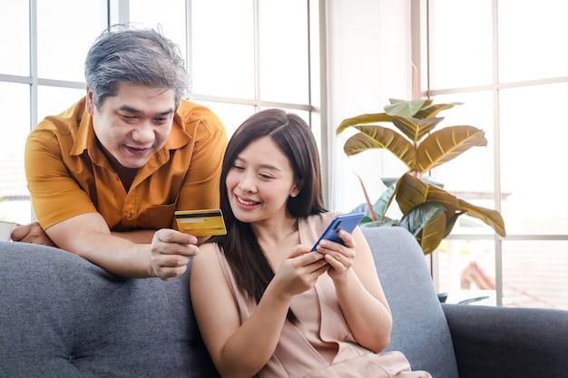 Azjatycka para trzymająca kartę kredytową i smartfona, aby zamówić online, zamiast wychodzić z domu. samoobrona, zostań w domu podczas rozprzestrzeniania się koronawirusa. dystans społeczny