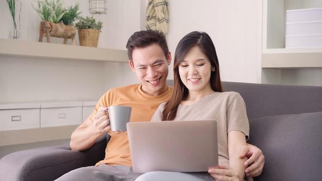 Azjatycka para używa laptop i pijący ciepłą filiżankę kawy w żywym pokoju w domu, słodka para cieszy się